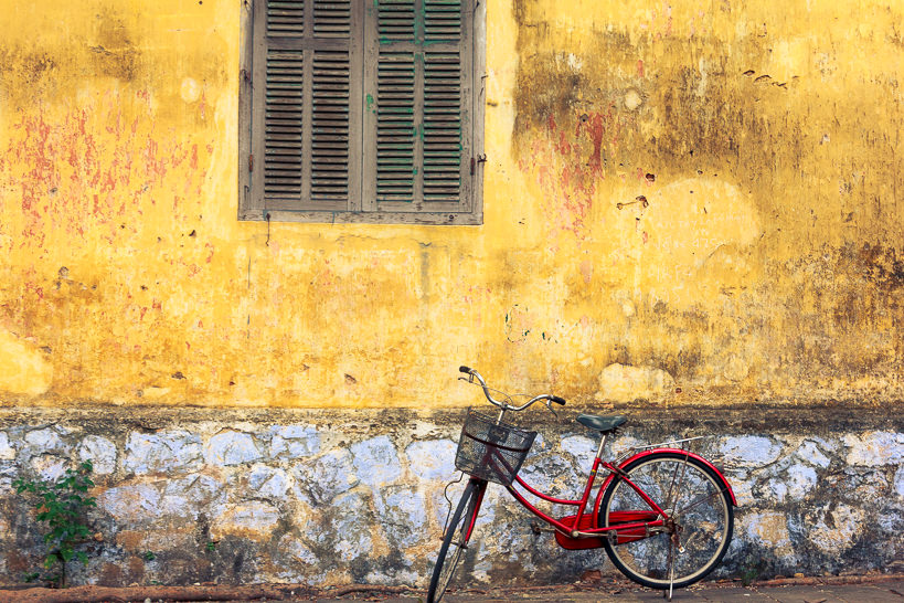 Red Vietnamese Bicycle against a yellow wall